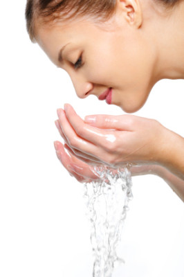 female washing her face with water